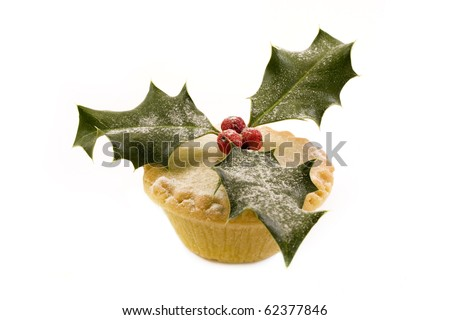 single mince pie decorated with holly over white