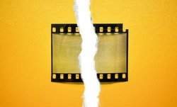 single 35mm dia film frame with empty cell on yellow paper background and torn paper edge effect, cool social media photo placeholder.