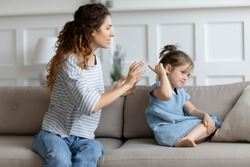 Single mother and little kid sit on couch at home, parent scolds preschool daughter teaches naughty mischievous child. Concept of punishment, bad behaviour misbehave of infant, upbringing difficulties