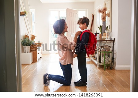 Single Mother At Home Getting Son Wearing Uniform Ready For First Day Of School Foto d'archivio ©