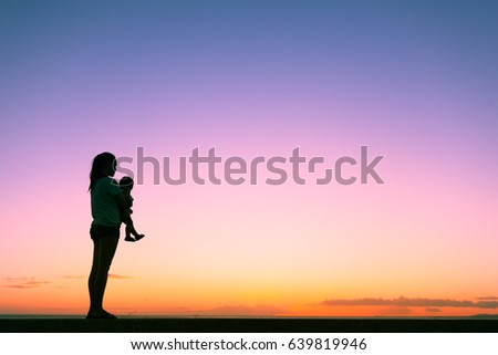 Single mother holding her baby child watching the sunset.  ストックフォト ©