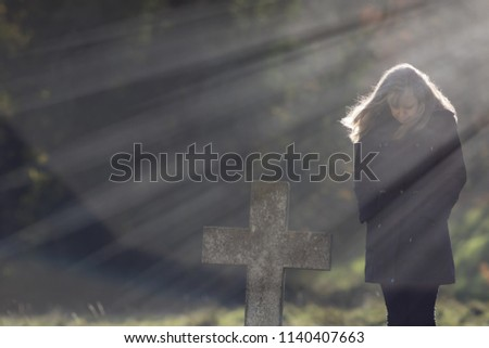 Single Mourner. Social distancing burial. Heavenly rays of sunshine behind grieving widow in cemetery. Mourning lady dressed in black contemplating life and death by the stone cross of a grave.