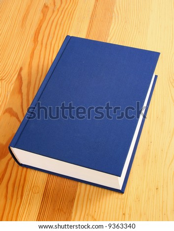 single navy blue book over wooden background