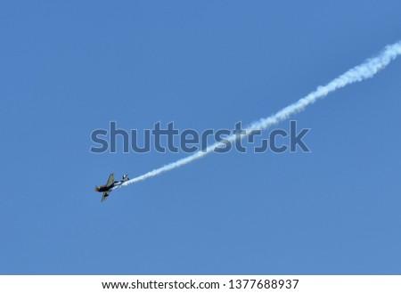Single one sport plane of aerobatic team vapour trails in blue sky. Plane white vapour trails tracks background. Plane aerobatic maneuver stunt. Budapest, Hungary.