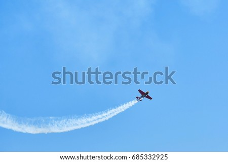 Single one sport plane of aerobatic team vapour trails in blue sky. Plane white vapour trails tracks background. Plane aerobatic maneuver stunt. Stunt planes aerobatic team vapor trails MAKS-2017