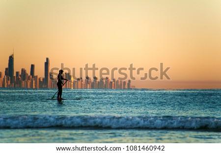 Single paddler against the Gold Coast skyline at sunset. #1081460942