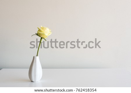 Single pale yellow rose in small white vase on table against neutral wall background with copy space #762418354