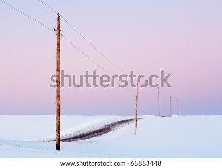 Single phase electrical power lines through an empty snow landscape against a pink sky.