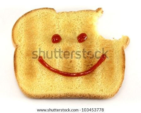 Single piece of toasted bread with a bite and drawn happy face isolated on white background.
