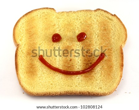 Single piece of toasted bread with a drawn happy face isolated on white background.