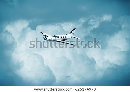 Single piston aircraft. Single-propeller aircraft flying over the blue sky. Single turboprop aircraft.. Small private plane flying in blue clouds.