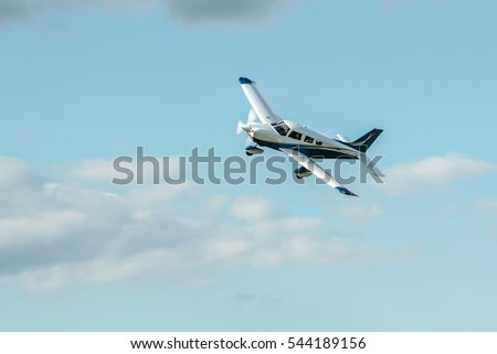 Single piston blue aircraft. Single-propeller aircraft flying over the blue sky at a small airport