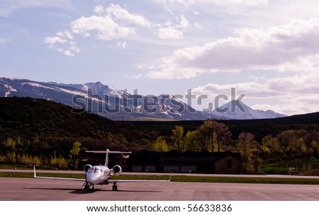 single private jet on tarmac with mountains in background