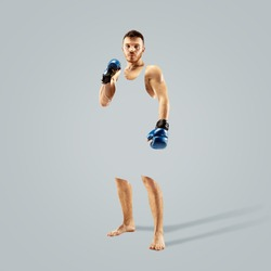 Single professional fighter isolated on grey studio background. Fit muscular caucasian athlete or boxer fighting. Sport, competition, human emotions, advertising concept. Abstract design.