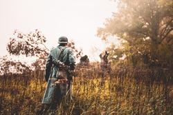 Single Re-enactor Dressed As German Wehrmacht Infantry Soldier In World War II Walking In Patrol Through Autumn Forest. WWII WW2 Times.