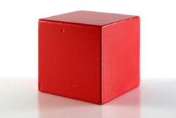Single red cube on reflective surface. White background.