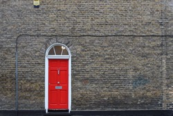 single red door on brick wall