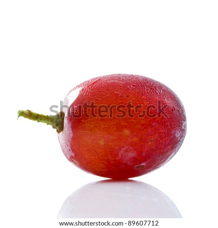 Single red grape on white table