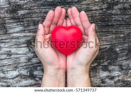 Single red love heart on female hand support on aging old wood for promoting congenital heart defect awareness week, American heart month and National Wear Red Day for women's health care concept