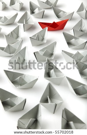 single red paper boat between lots of gray paper boats