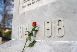 Single red rose placed against marble Great War soldier memorial on Sunday 11th November remembrance day for those who lost their lives 1914 1918