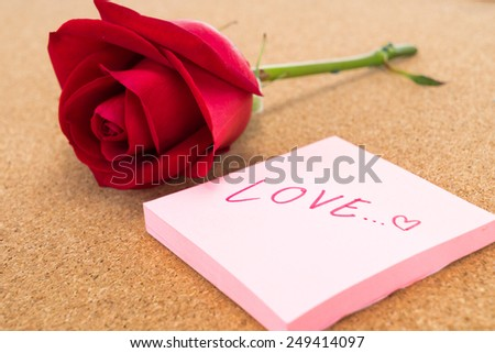 Single red rose with post it with word \