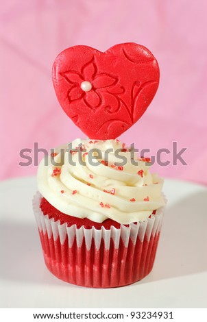 Single red velvet cupcake with white butter cream frosting and a fondant heart placed on top, presented on a serving plate with a pink background.