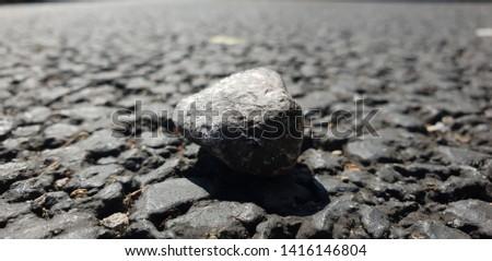 Single rock on a single street/road.