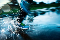 Single runner running in rain and making splash in puddle