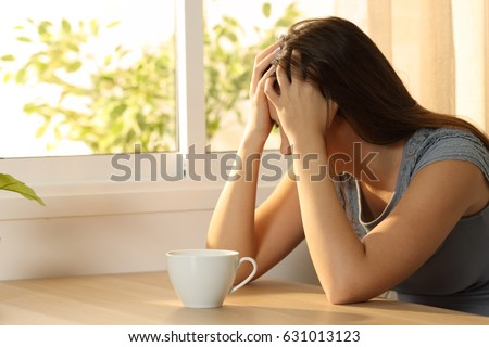 Single sad woman covering face sitting in a table at home