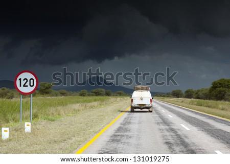 Single safari car traveling in Africa. Namibia. Dark, storm sky.