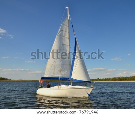 Single sail boat on the lake. People faces unrecognizable.