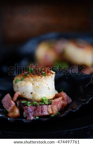 Single sauteed scallop with chives are pork largons in black scallop shells against a dark, rustic background. The perfect image for your fish restaurant menu cover design. Copy space. #474497761