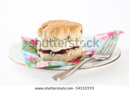 Single scone with cream and strawberry jam filling on plate with fork