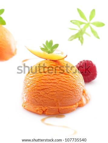 Single scoop of a colourful orange tropical mango icecream dessert on a white background