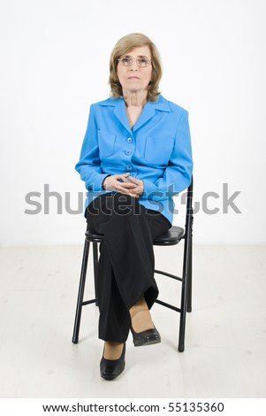 Single senior business woman sitting on chair at conference listening and looking serious