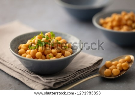 Single serving of chickpeas in pretty grey bowl on linen napkin garnished with parsley