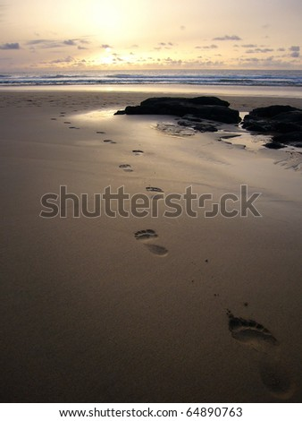 Stock Photo Single set of footprints in the sand walking towards sunset at the beach of Fuerteventura, Spain.