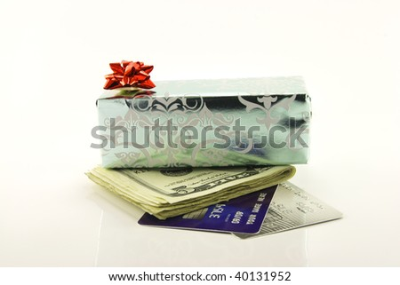 Single shiny silver gift with a red bow, dollars and plastic credit cards on a reflective white background