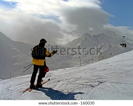 single skier looking downhill in alps
