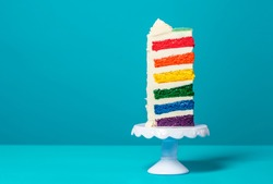 Single slice of birthday cake on a white cakestand minimalist on a blue background. Homemade cake with multicolored layers and buttercream