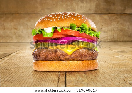 Single solo burger hamburger cheeseburger on table wooden surface delicious perfect deluxe sandwich