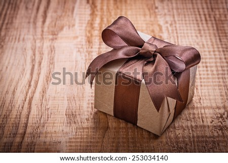 single square vintage gift box qith brown bow on old wooden board