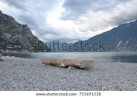 Single stone bench on shore of calm lake and mountains #715691518