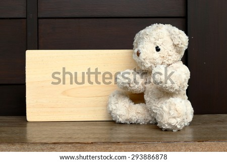 Single teddy bear on a grass and board wood for your text.