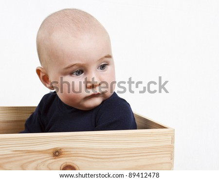 single toddler with dark shirt in wooden box looking to the right.