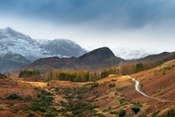 Single track road leading through rural countryside with snowcapped mountains and dark Winter clouds. Langdale, Lake District, UK.