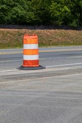 Single traffic barrel dividing an asphalt roadway, traffic safety creative copy space, vertical aspect