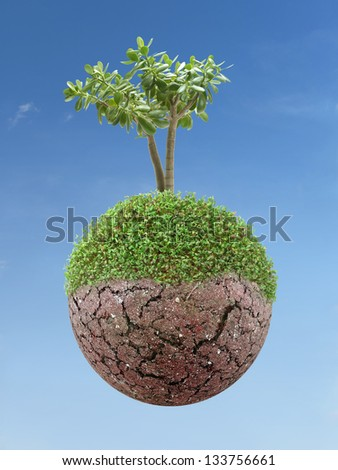 Single tree growing on small semi-green planet over blue sky