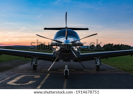 Single turboprop aircraft on evening runway after sunset. A single-engine plane is parked on the runway, bathed in the evening sun. Beautiful color view of the plane.
